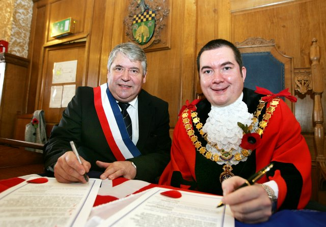 Mayors Alain Bezirard, left, and Chris Harbron sign the twinning charter