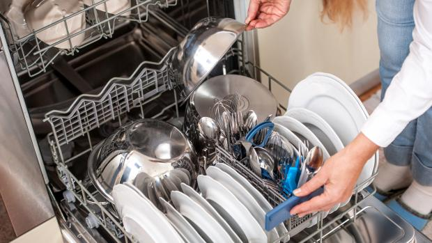 Craven Herald: This dishwasher looks like it's already full, but the owner can't resist adding another bowl. Don't do this if you want your dishes to get clean. Credit: Getty Images / CasarsaGuru