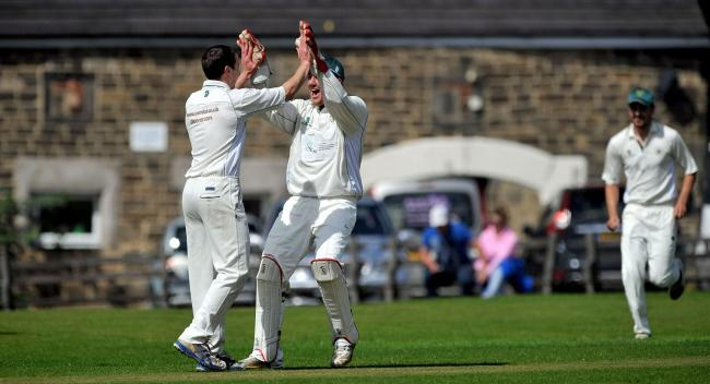 Jim O'Hara and Dom Bennett celebrate a wicket for Crossflatts, but they will be doing that in the Bradford League rather than the Craven League in 2021. Picture: Andy Garbutt.