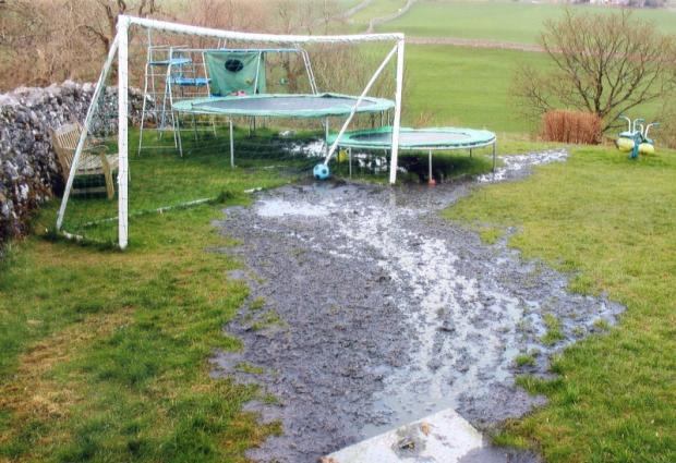 Sewage covers a garden in Badger Gate, Threshfield, where children play