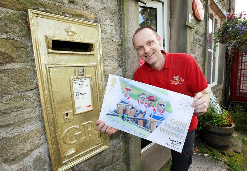 Upper Wharfedale postman Alan Wain with a giant version of the special stamp, featuring Andy Hodge, at the gold postbox in Hebden