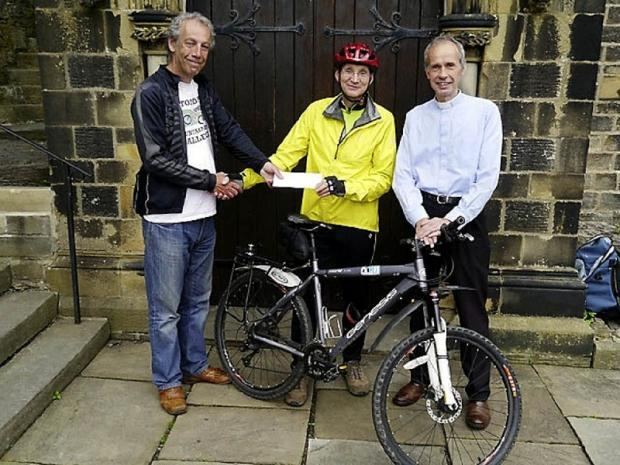 Coast to coast cyclist Graham Reay, centre, with BeCycling for Africa founder Chris Armstrong (left) and David Griffiths, vicar of St James' Church in Silsden