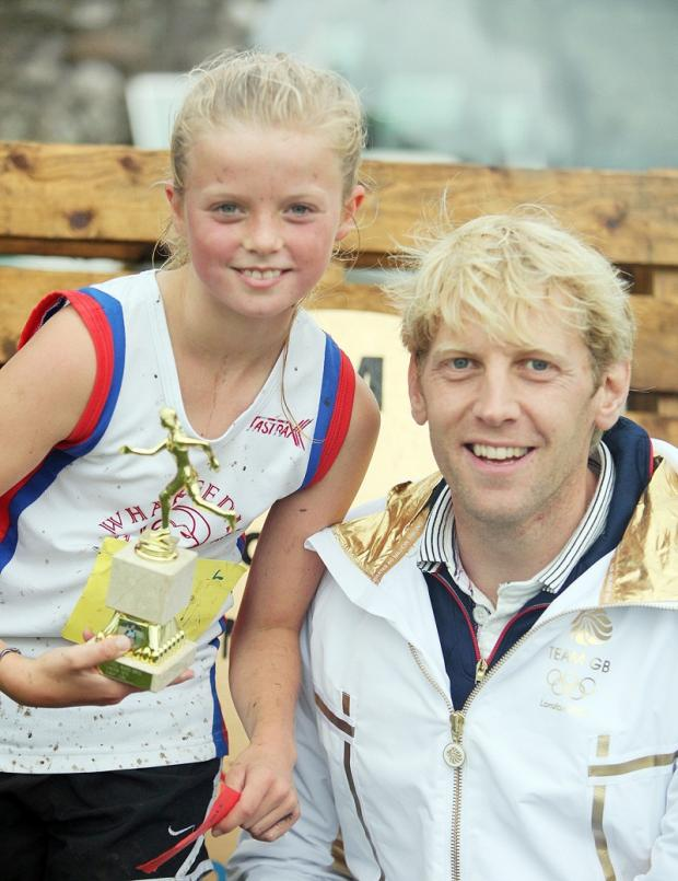 TROPHY: Andy Hodge with under-12s girls' fell race winner Shona Hastings
