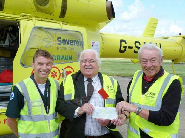 Former Craven District Council chairman Andy Quinn (centre) hands over a fundraising cheque to the Yorkshire Air Ambulance charity