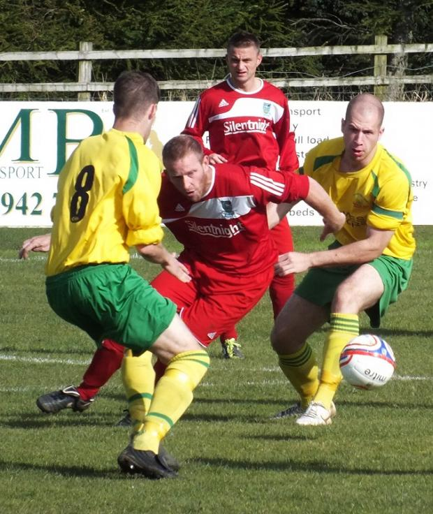 Barnoldwick Town's Stewart Airdrie weaves his way through some heavy traffic