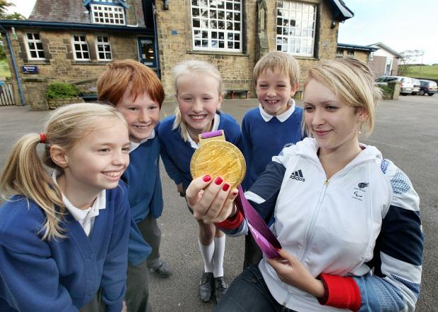 Former Lothersdale Primary School pupil and Paralympic gold medalist Danielle Brown visits her old school to show pupils her gold medal. Picture shows Beth Norton, Reuben Riddiough, Nell Wiseman and Sam Winter with Danielle