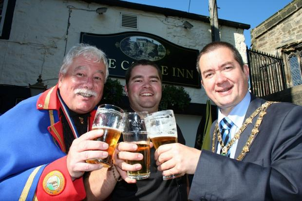Kevin Griffiths, left, poses with a pint after the Olympic torch parade through Skipton in June. Also pictured is Calvin Dow from the Castle Inn, where the picture was taken, and former town mayor and current district council chairman Chris Harbron