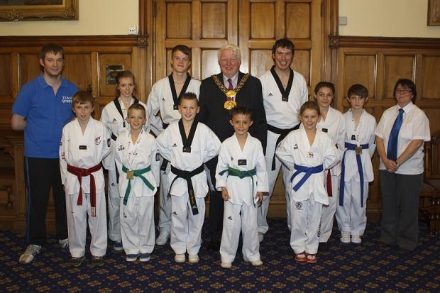 Craven Herald: The Lord Mayor of Bradford, Councillor Dale Smith, welcomes coach Rick Simpson, left, and members of Quest Taekwondo Club to a civic reception at Bradford City Hall after their national championship success