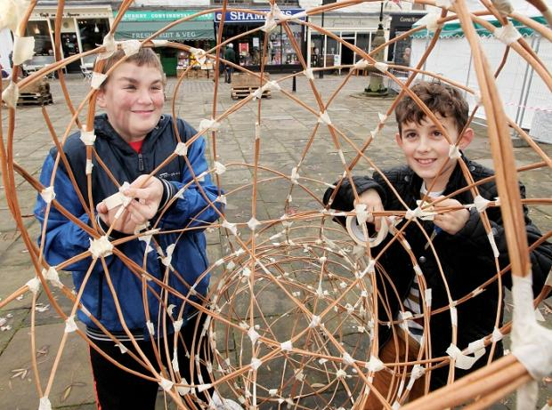 Liam Pickering and Jordan Hawkins putting the finishing touches to a paper lantern in Barnoldswick town square