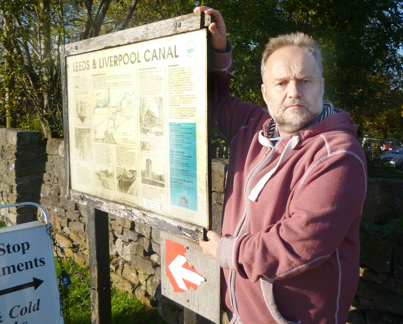 Coun David Whipp with a neglected notice board at Greenberfield Locks