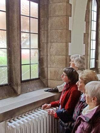 Members of the congregation view the damaged windows