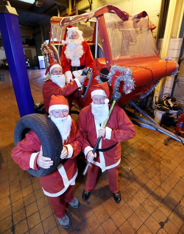 Craven Herald: Skipton and Craven Rotary Club members make running repairs to Santa's sleigh in preparation for their tour of the town. Pictured are David Mitton, Colin Hargreaves, Ted Lee and Ian Thwaites