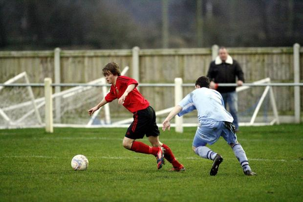 Silsden scorer Chris Wademan takes on a Maine Road opponent