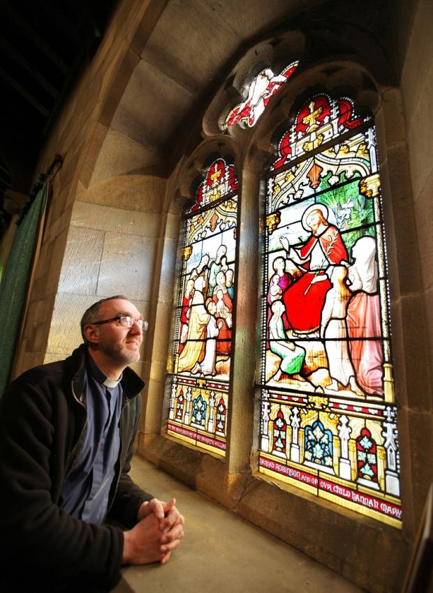 Rev Stuart Stobart viewing one of the windows which date from 1891