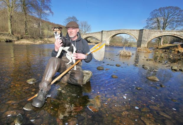 Bolton Abbey Estate river-keeper Mark Whitehead with his dog Todd at Barden Bridge