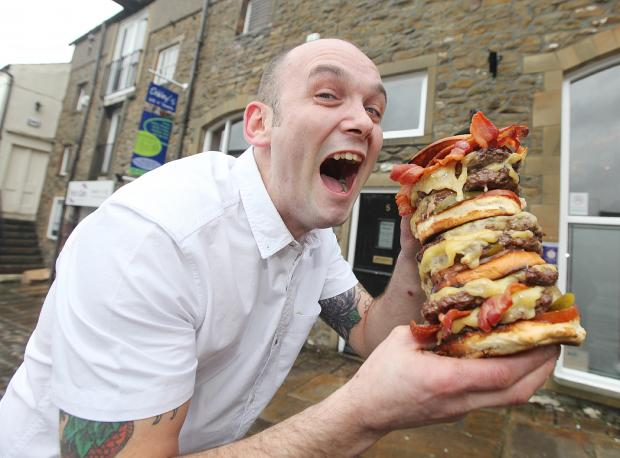 Oakley's restaurant owner Jamie Oakley tucks into a mammoth cheese burger