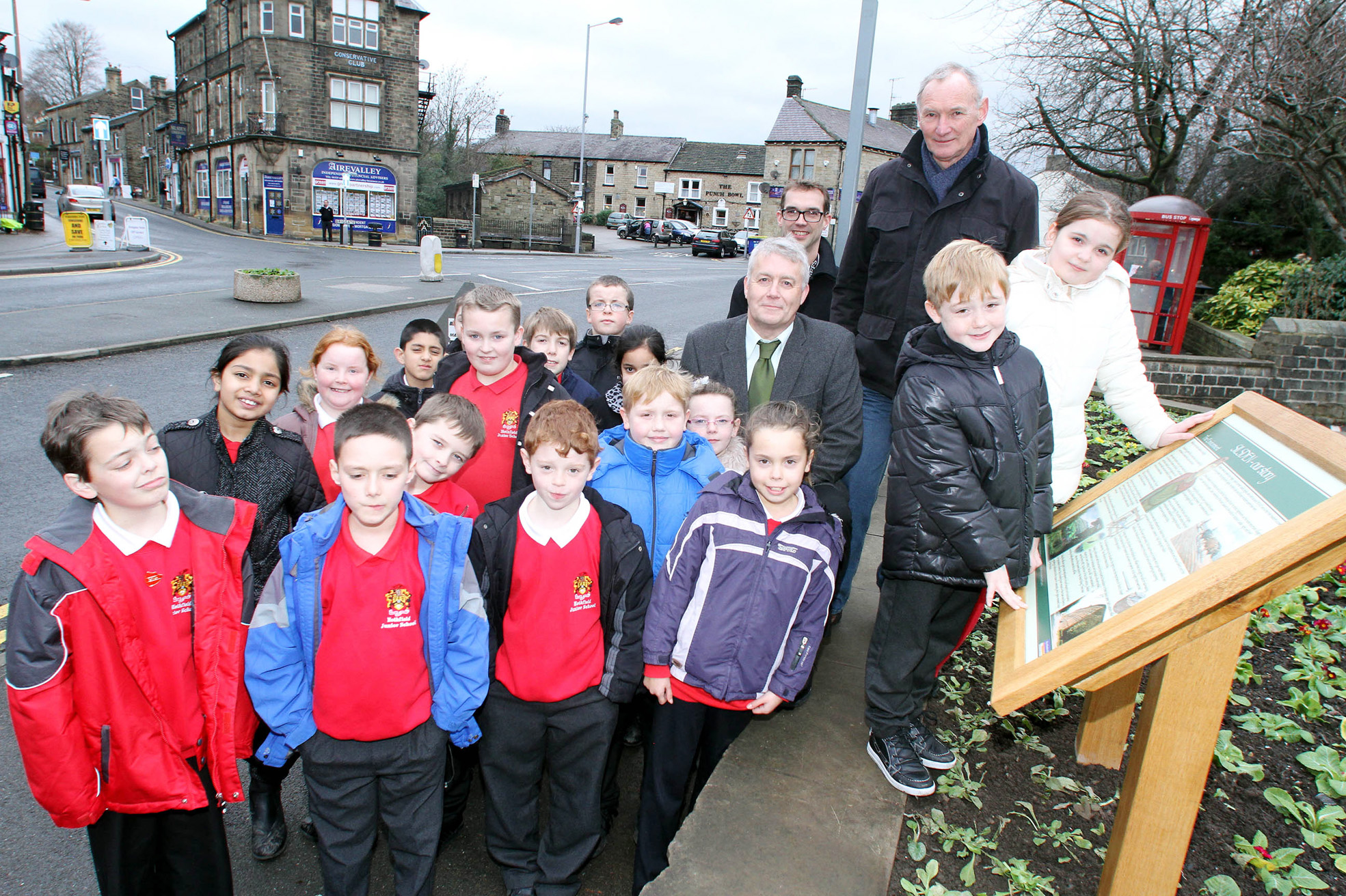 Charlie Driver and Laila Heslop, of Hothfield Junior School's archaeology club, look at the information board with Councillor Andrew Mallinson (centre) David Mason of Silsden Local History Group, children from the school and headteacher James Procter