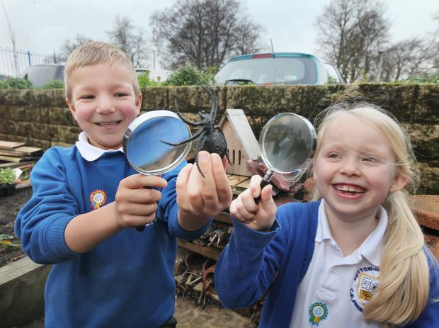 Craven Herald: Sutton Church of England Primary School's George Little and Millie Brookbank outside the bug hotel