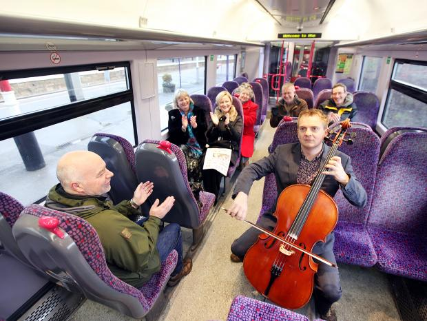 Musical director of Skipton Camerata Ben Crick playing to commuters on the Skipton to Bradford  train