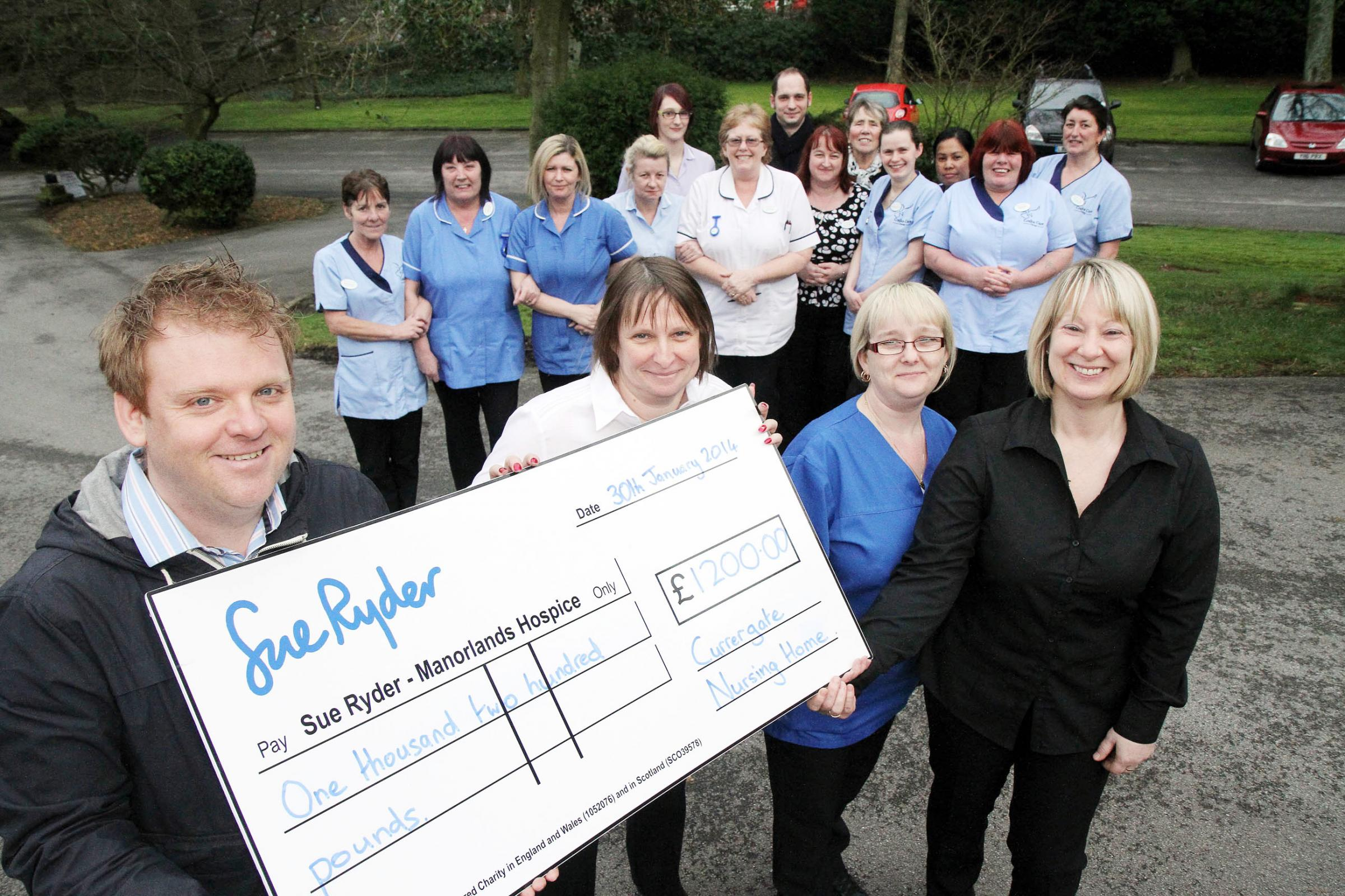 Manorlands fundraiser Andrew Wood, left, receives the cheque from staff at Currergate Nursing Home, Steeton