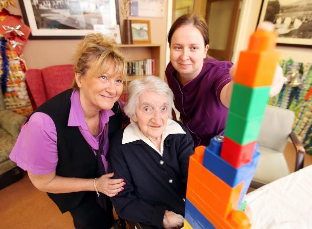 Sharon Slingsby and Gosia Nowotny help 105-year-old Mabel Arnold in a co-ordination therapy session at the Gills Top care home