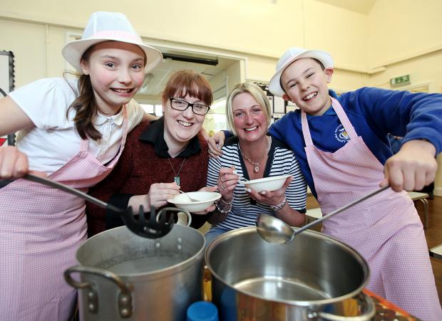 Pupils Megan Baines and Edward Bradley serve lunch to Georgina Dunkerley and Adele Booth during the community session at the school