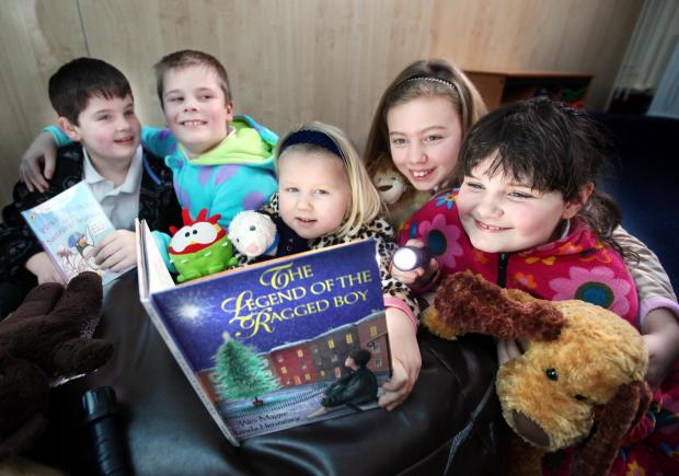 Chris Wright, Bobbie Ratcliffe, Isla Dawson, Rosie Chapman and Emma Wright reading bedtime stories by torchlight
