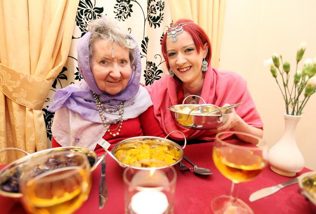 Edith Shaw is served Indian food by care leader Jass Harmson
