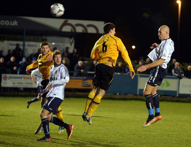 Craven Herald: Guiseley's Danny Ellis powers in their equaliser from Wayne Brooksby's corner