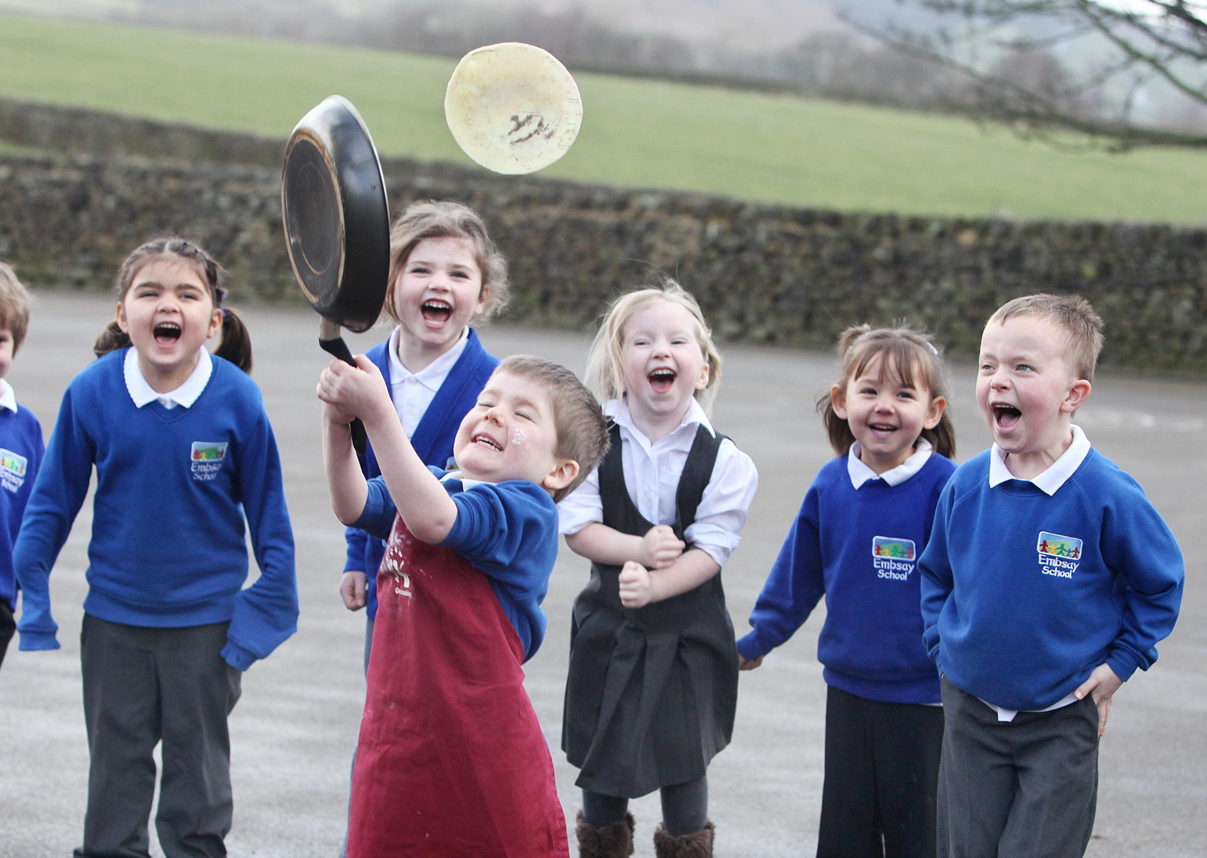 Embsay Primary School's Will Snowden flips the pancake cheered on by classmates