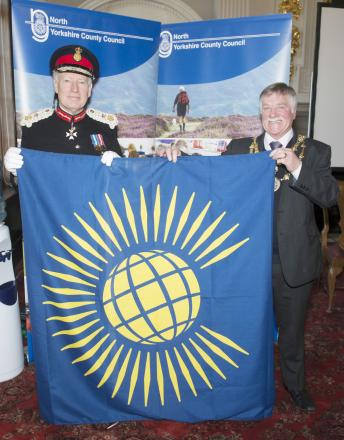 Coun Donny Whaites and the Lord Lieutenant of North Yorkshire, Lord Crathorne show off the Commonwealth flag