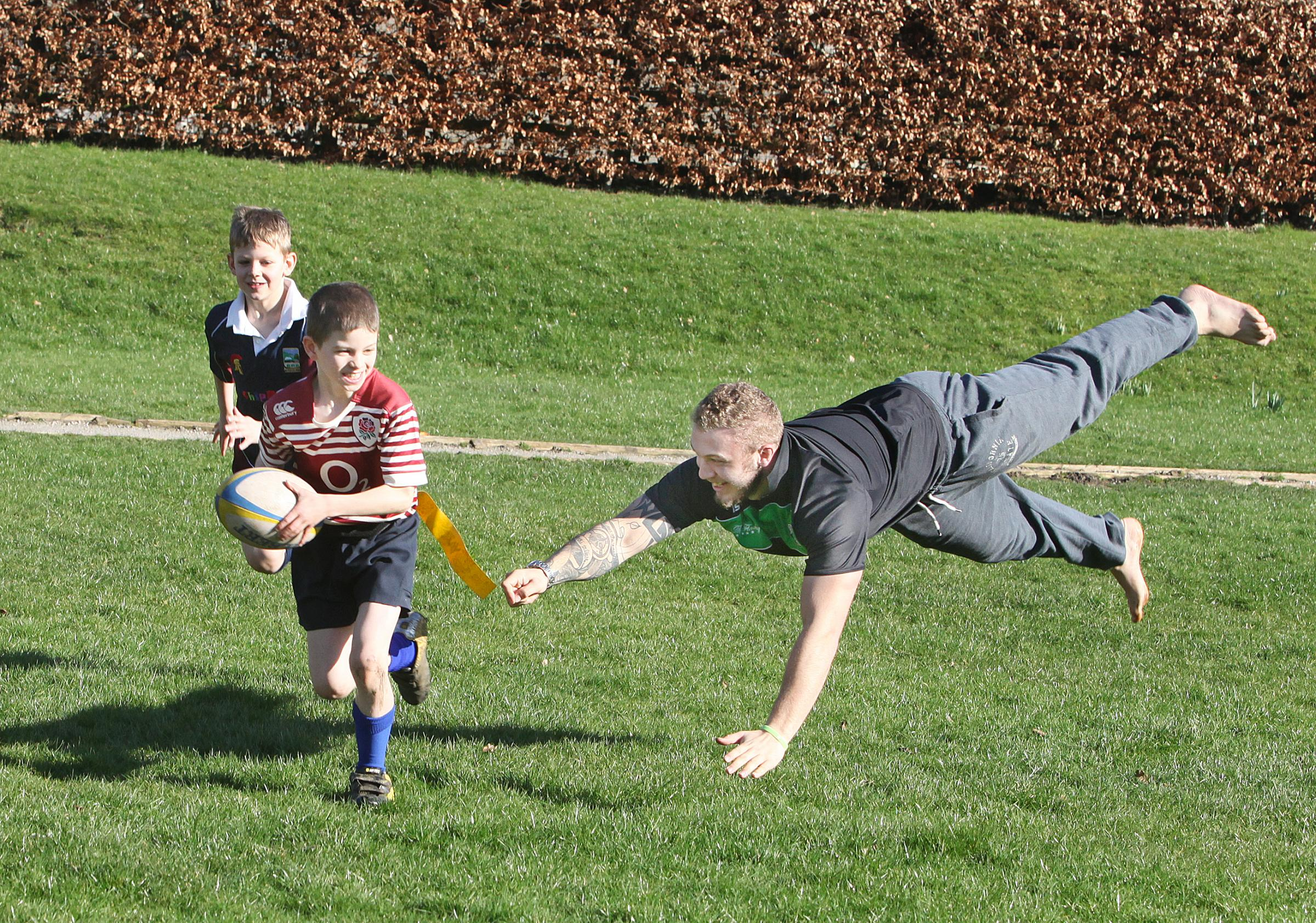 England and Leeds rugby star Chris Walker makes a grab for Jake Wright's tag, with Elliot Marklew in support