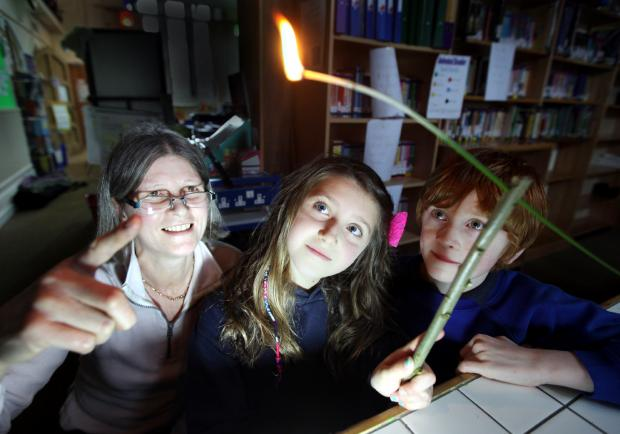 Craven Herald: LIT UP: Eco farmer Fiona Clark shows Kettlewell Primary School pupils Mia Proctor and Ben Newey an 18th century reed lamp.