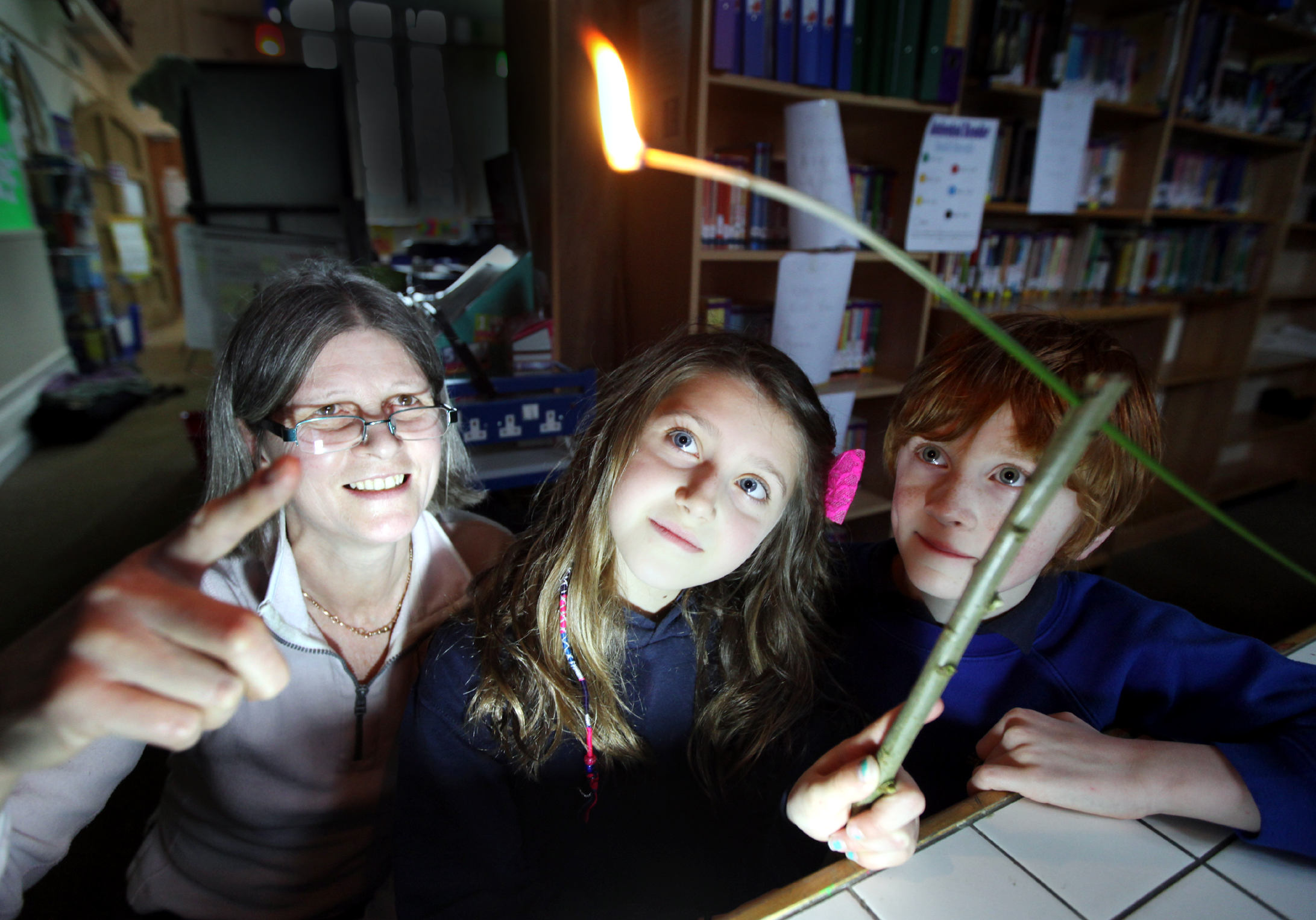 LIT UP: Eco farmer Fiona Clark shows Kettlewell Primary School pupils Mia Proctor and Ben Newey an 1