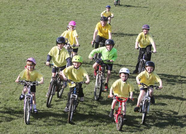 READY FOR THE OFF:  Skipton Rotarian David Goldie with pupils in yellow jerseys from Greatwood Primary School as they prepare for the Rotarians' Tour de Mart junior cycle event