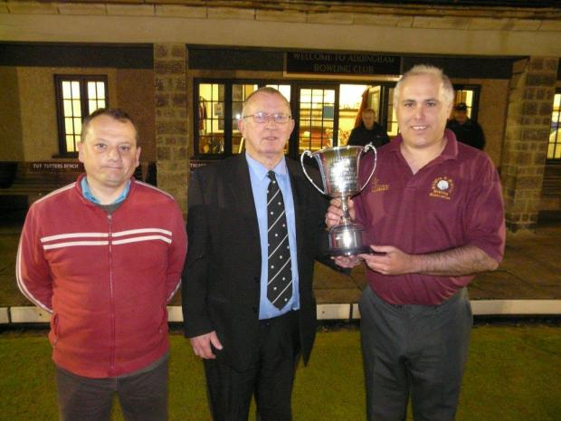 Craven Herald: CUP JOY: Peter Clark, right, receives the cup from Skpiton League president who is flanked by the competition runner up Martyn Loftus