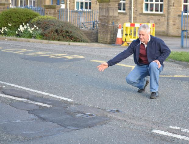 Craven Herald: DANGER CLAIM: Coun Chris Moorby inspects the road outside Hellifield Primary School