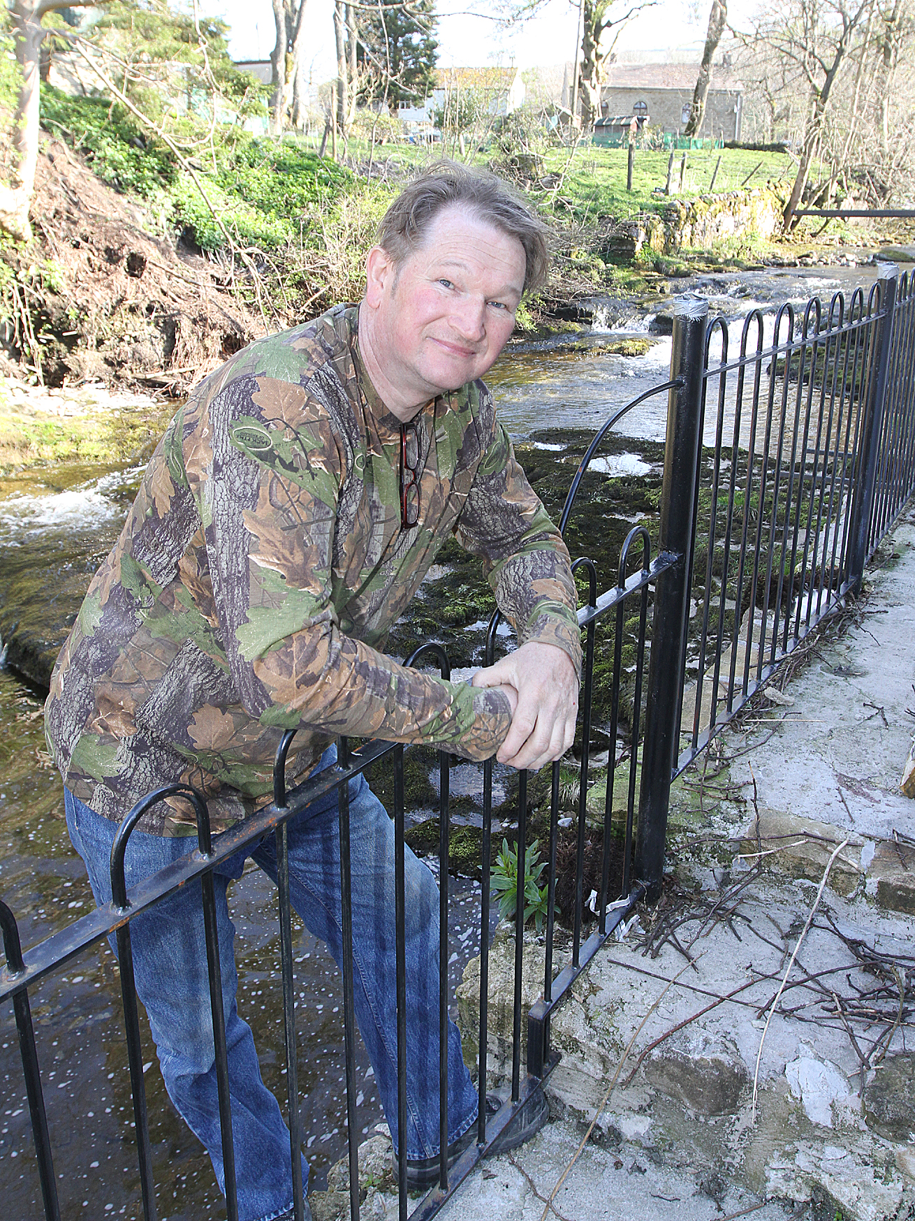 BOUNDARY: Matwey Kozlow leans on the fence he built outside his house in Kettlewell, with the stream behind him