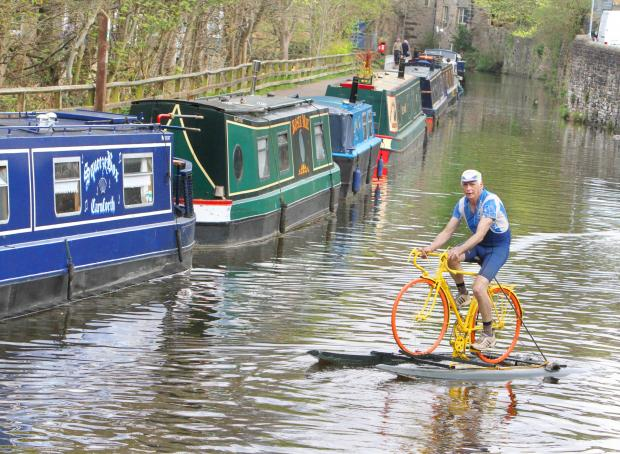 Craven Herald: WATER WHEELS: Ian Clark from Pennine Cruises on his Tour de Cut bike, pedalling along the Leeds to Liverpool Canal.