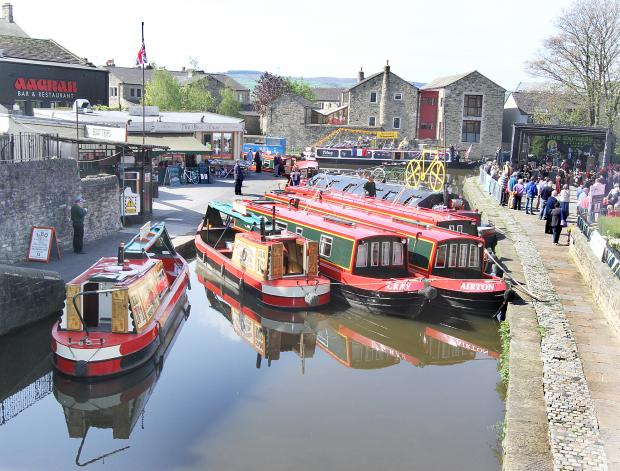 Craven Herald: Decorated boats in the canal basin while activities go on around them