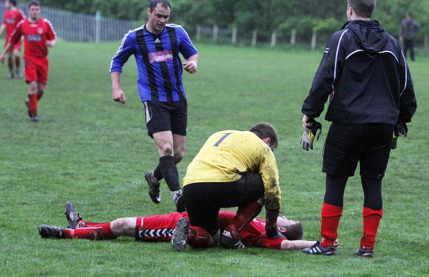 Players rush to the aid of Cross Hills player Luke Newton, after he was left sprawled on the turf following a collision during the cup final match between his side and Skipton LMS