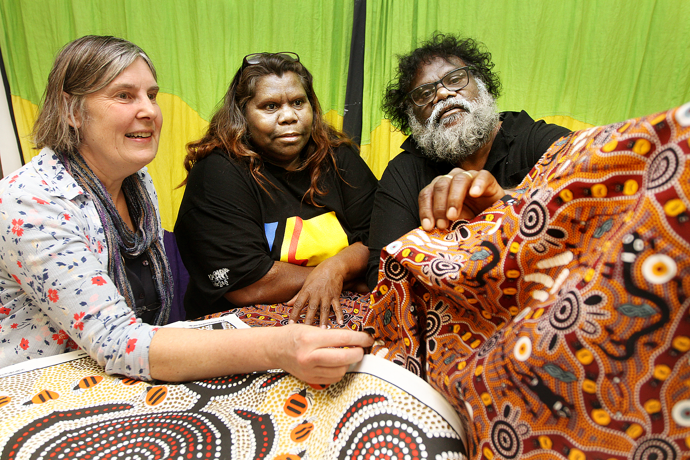 Geoffrey and Annette Stokes, of the Wongutha Tribal Group, viewing textiles at the Looking Well community arts centre in Bentham, with Alison Clough