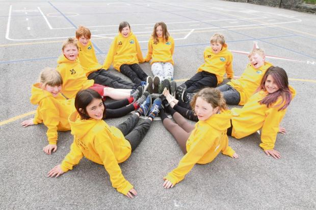 Craven Herald: Kettlewell School pupils Kelpha Tripathi, Rebecca Scott, Lewis Needham, Ben Newey, Ella Blundell, Daisy Whitaker, Harry Simpson, George Simpson, Mia Proctor and Emma Falshaw receive yellow hoodies from the school's PTA as part of the Grand Depart cele