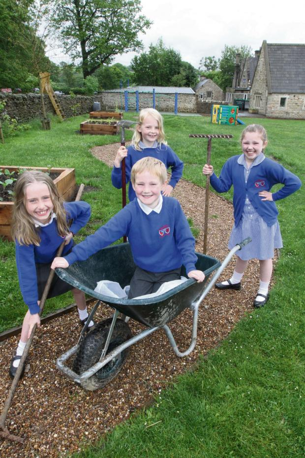 Craven Herald: Boyle and Petyt pupils with the help of teachers and parents, lay a path and planting boxes in the school garden. Picture shows Bella Kaye, Harrison Bonne, Kitty Cray anmd Daisy Newton who helped on the project. (6827596)