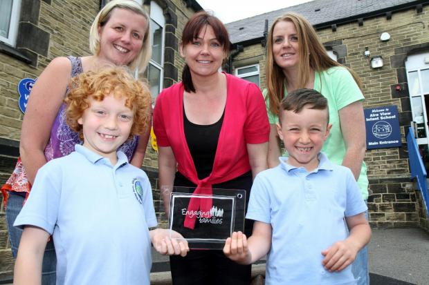 Celebrating Aire View Infant School's award are pupils Alfie Liddle, left, and Huey Cunningham with, from left, Charlotte Inman, Sharon Grimshaw and Kelly Coburn