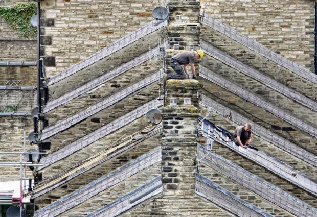 Garnetts Year -    A  pair of roofers from Tidswell Roofing ply their trade working on the  Geometric angles of roofs stack in rows in Middletown , Skipton  (8182974)