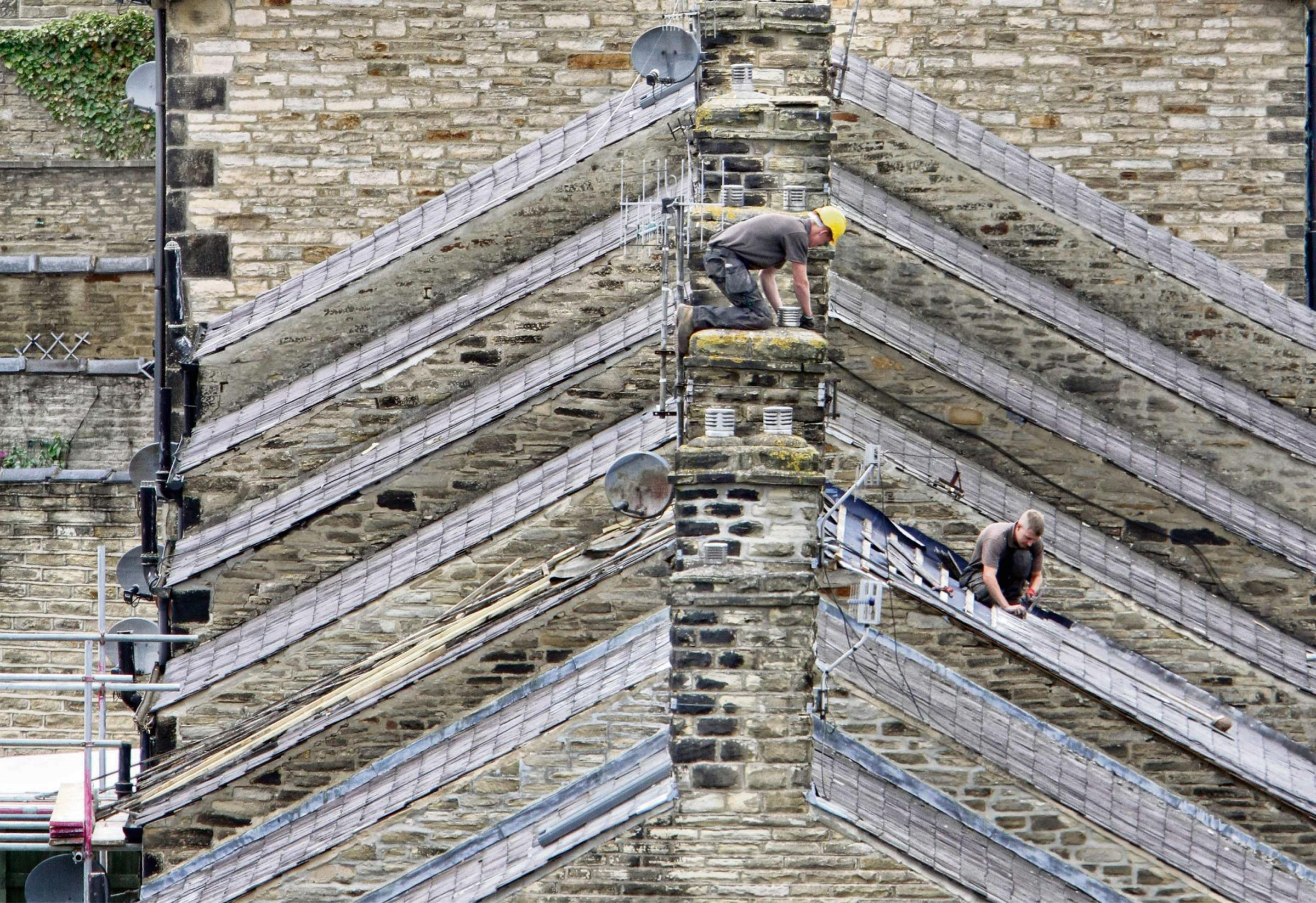 Garnetts Year -    A  pair of roofers from Tidswell Roofing ply their trade working on the  Geometric angles of roofs stack in rows in Middletown , Skip