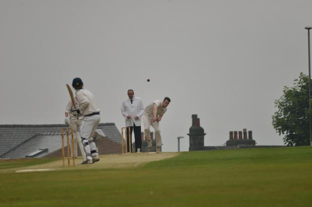 Ilkley's Henry Wilson bowls in the gloom at Rawdon