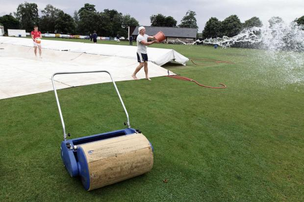 There may have been play in the semi-finals of the Waddilove Cup and Birtwhistle Cup on Sunday but not everyone was so lucky on Saturday. Here Settle's Tom Davidson throws a bucket of water off the covers in what proved a vain bid to start their home