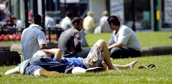 People resting in a park in hot weather